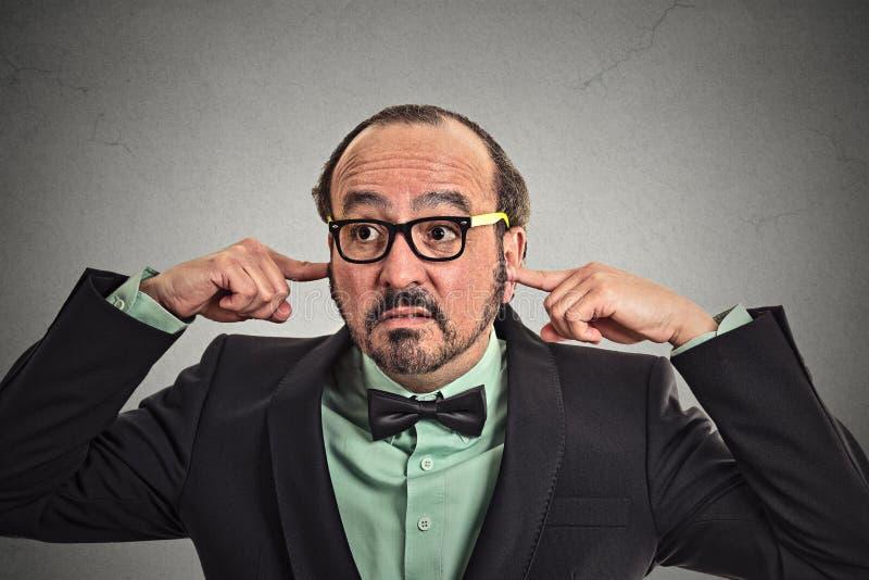 Geërgerde rijpe mens met glazen die oren met vingers stoppen stock fotografie