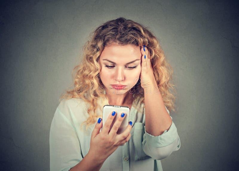 Geërgerde vrouw, boos weg door wat zij op haar celtelefoon zag stock afbeelding