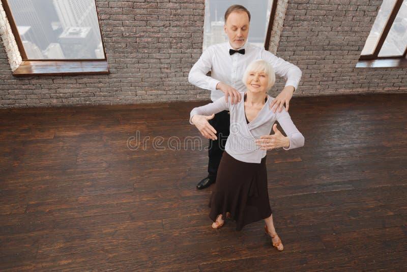 Geïmpliceerd bejaard paar die in interactie in de dansstudio presteren royalty-vrije stock afbeeldingen