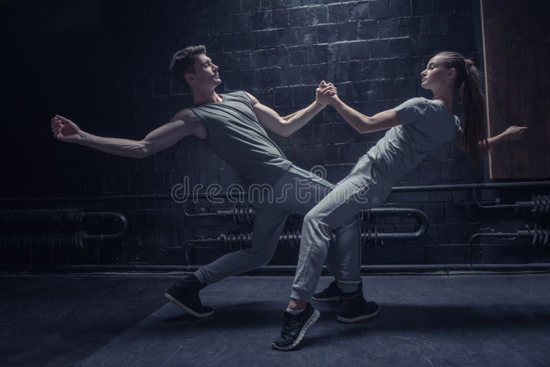 Geïmpliceerde dansers die in dichte interactie met elkaar opwarmen stock afbeelding