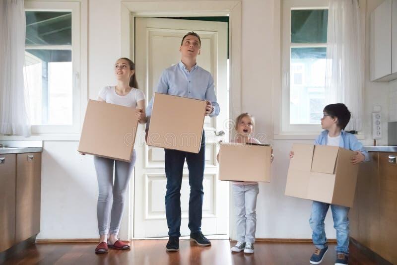 Geïmponeerde familie dragende dozen die zich binnen aan nieuw huis bewegen royalty-vrije stock foto's