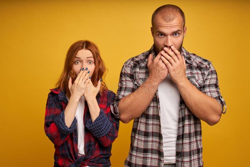 Geïmponeerde jonge aantrekkelijke vrouwelijke en mannelijke losse toespraak twee van angst, dekking mouthes met beide palmen die, stock foto
