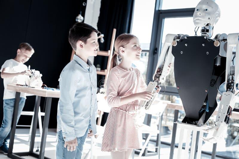 Geïmponeerde kinderen die terwijl robot in workshop onderzoeken royalty-vrije stock fotografie