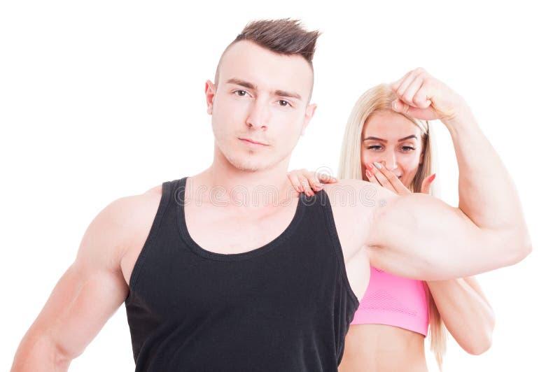 Geïmponeerde vrouw door persoonlijke trainerspieren stock afbeelding
