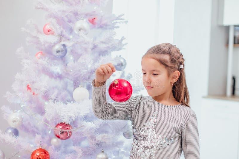 Geïnspireerd kind staat vlak bij kerstboom en kijkt naar haar reflectie in roze glas bauble stock foto