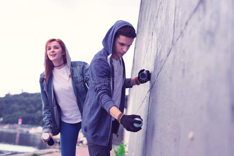 Geïnspireerde donker-haired kerel die graffiti kunstenaar en het schilderen concrete oppervlakte zijn stock foto's