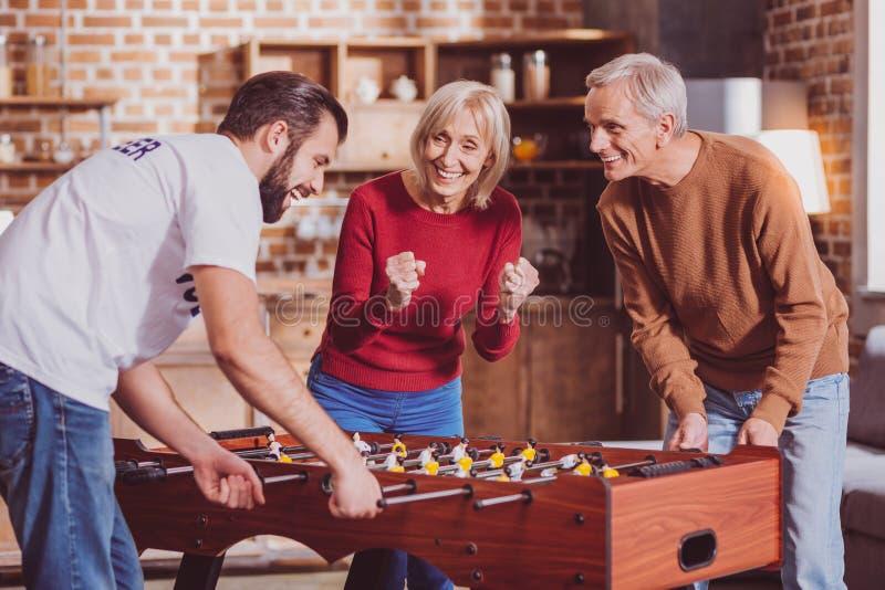 Geïnspireerde gepensioneerde die een spel met een jonge mens spelen royalty-vrije stock foto