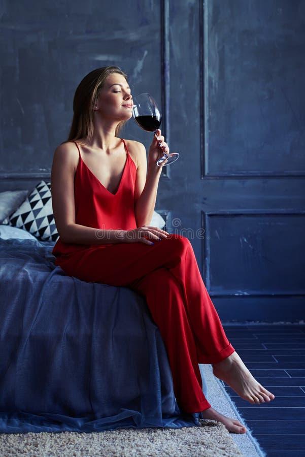 Geïnspireerde vrouw die van een glas rode wijn genieten terwijl het zitten op stock afbeeldingen
