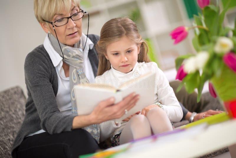 Geïnteresseerde het meisje bekijkt het boek terwijl de oma las royalty-vrije stock afbeeldingen