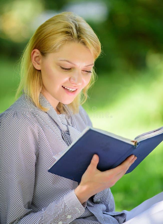 Geïnteresseerde het meisje zit de park gelezen achtergrond van de boekaard Het lezen van het inspireren boeken Vrouwelijke litera stock afbeelding