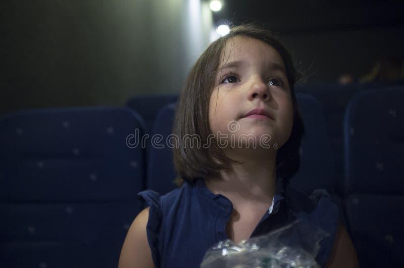 Geïntrigeerd kindmeisje bij bioskoop Echte scène royalty-vrije stock fotografie