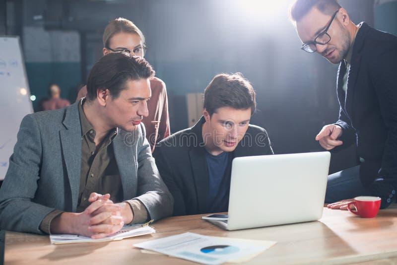 Geïntrigeerde partners die bij laptop letten op stock foto's