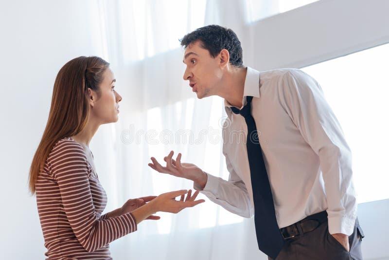 Geïrriteerde boze mens die argumenten geven aan zijn emotionele vrouw royalty-vrije stock fotografie