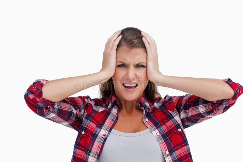 Geïrriteerde vrouw met de handen op haar hoofd stock afbeelding