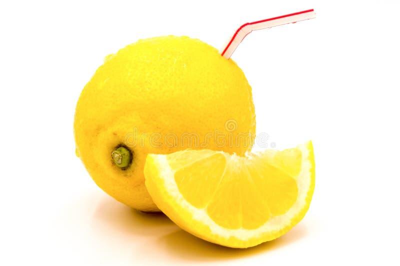 Geïsoleerd citroensap Een hele anderhalve citroen met stro stock afbeelding