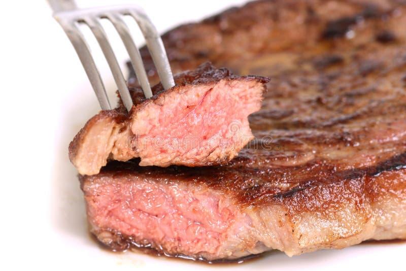 Geïsoleerd gediend stuk van middel geroosterd rundvleeslapje vlees op witte achtergrond royalty-vrije stock afbeeldingen