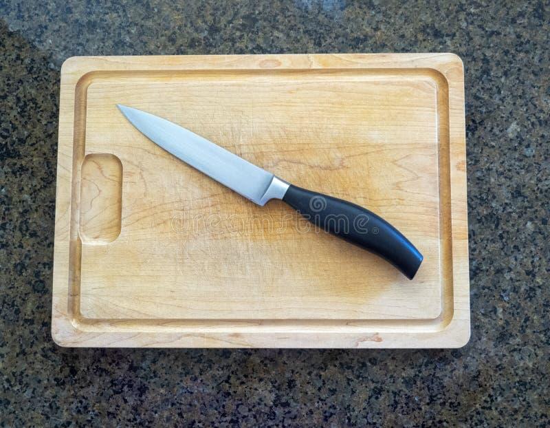 Geïsoleerd knippend mes op een groot houten scherpe raad met een teller van de granietkeuken stock foto's