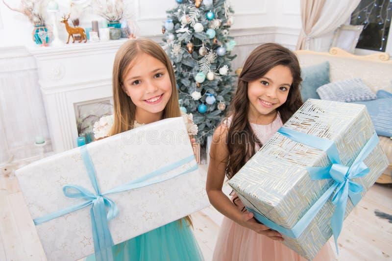 Geïsoleerd op witte achtergrond Leuk klein kinderenmeisje met aanwezige Kerstmis de gelukkige meisjeszusters vieren de wintervaka stock fotografie