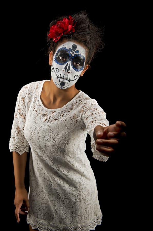 Geïsoleerd op zwarte met verdriet op haar gezicht, een mooie jonge vrouw met suikerschedel en bloemen in haar haar royalty-vrije stock foto
