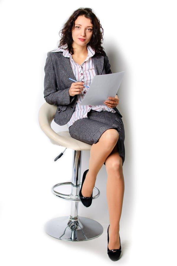 geïsoleerd over een witte achtergrond Het brunette loopt op een hoge stoel Hij houdt een blad van document en een ballpoint in va stock afbeelding