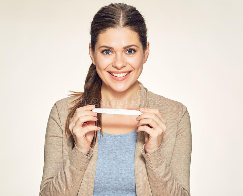 Geïsoleerd portret van glimlachende jonge vrouw die zwangere test houden stock foto