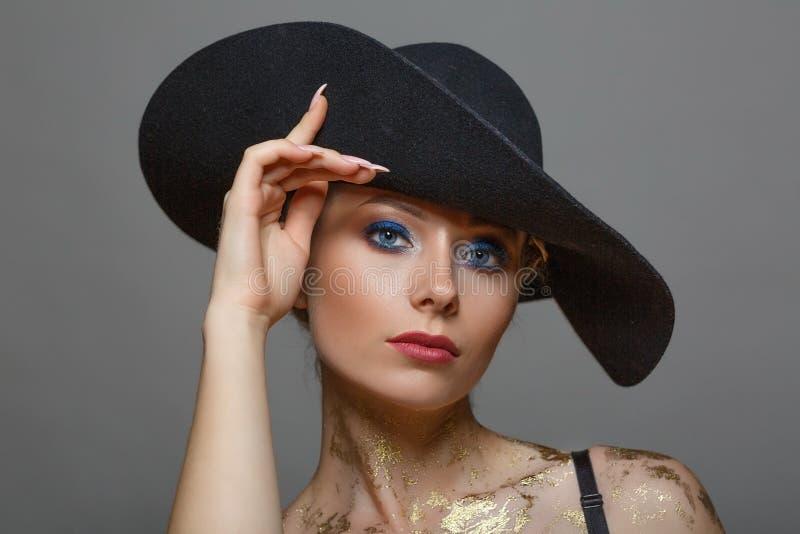 Geïsoleerd portret van mooie vrouw binnen met samenstelling in zwarte hoed op witte achtergrond, royalty-vrije stock fotografie