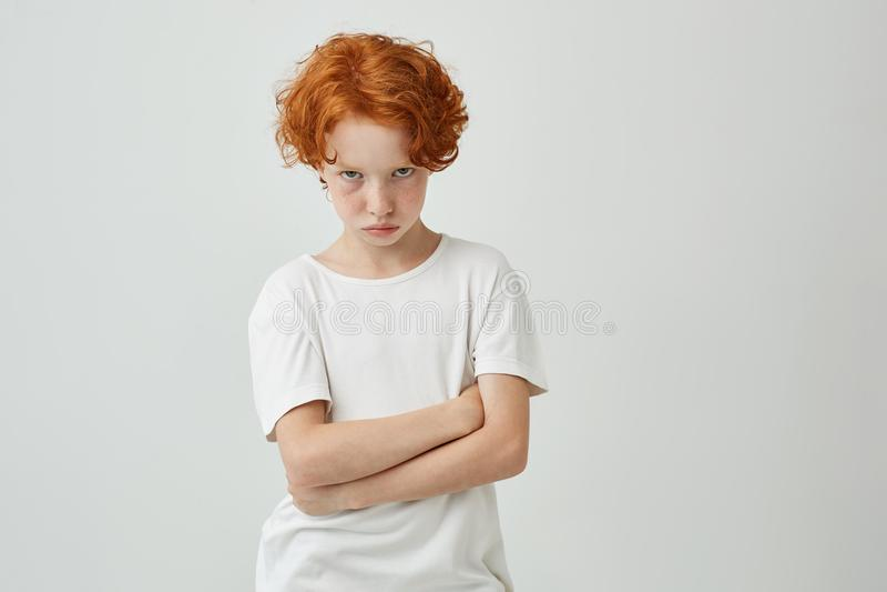 Geïsoleerd portret van ongelukkig weinig jong geitje met rode krullende haar en sproeten die door leraar worden beledigd die slec stock afbeelding