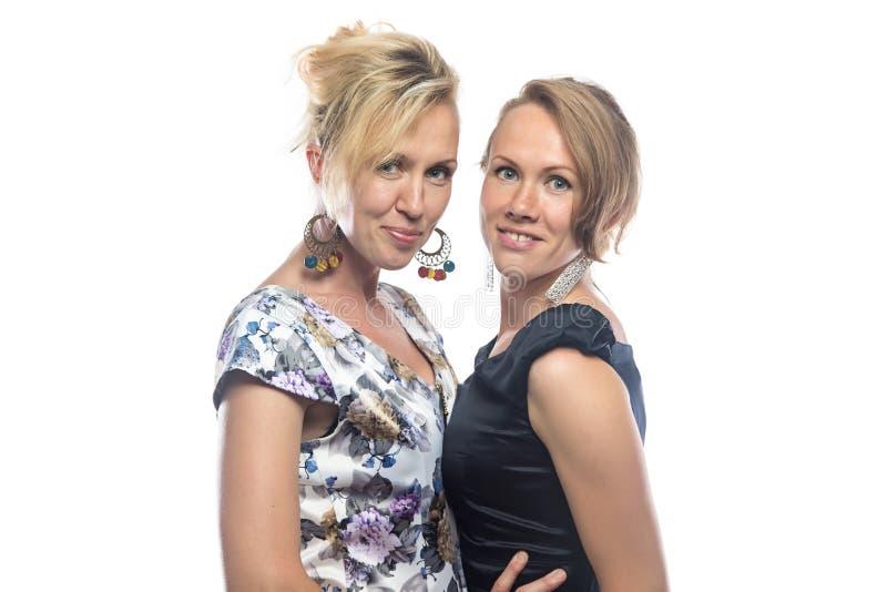 Geïsoleerd portret van twee bevindende zusters op wit stock afbeeldingen