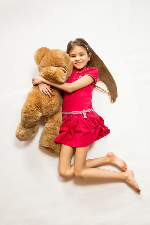 Geïsoleerd schot van leuk glimlachend meisje die in grote bruine teddybeer een gat maken stock foto