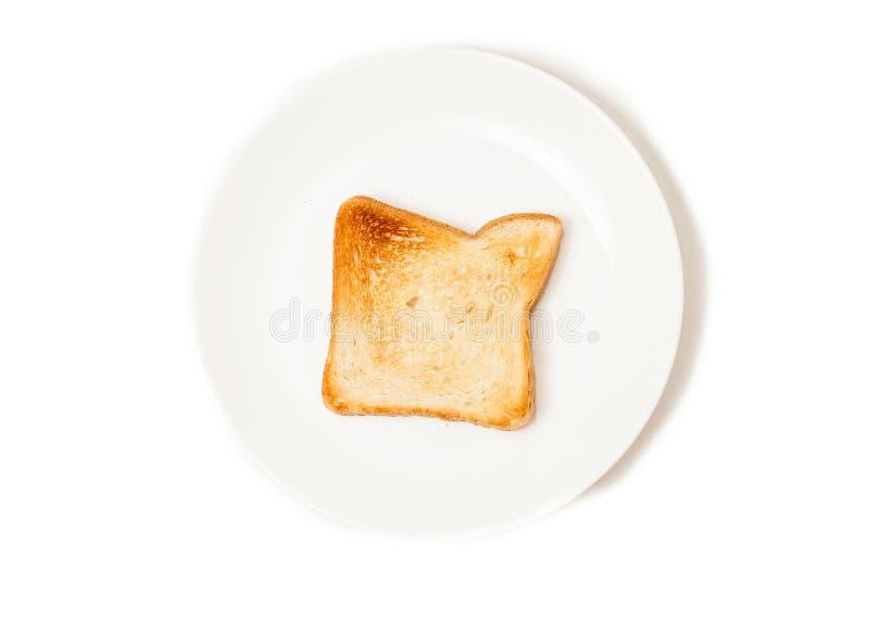 Geïsoleerd schot van verse gebakken toost op witte schotel stock afbeelding