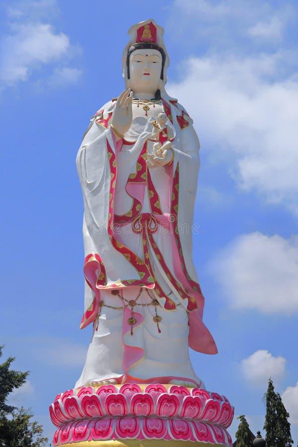 Geïsoleerd van het Grote standbeeld van Boedha van Guanyin bevindt de tribunereeks zichdie witte kleding met roze bevinden zich o royalty-vrije stock fotografie