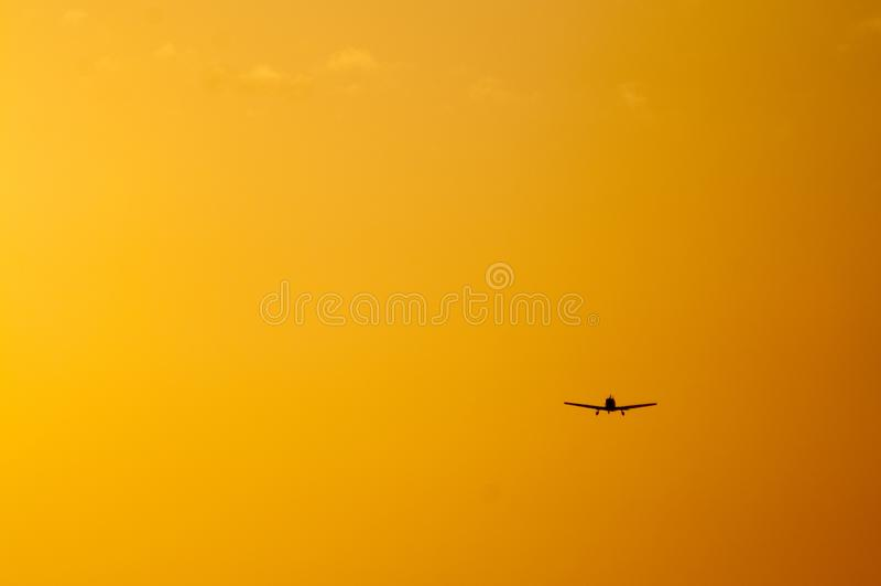 Geïsoleerd Vliegtuig bij zonsondergang op oranje hemel royalty-vrije stock afbeeldingen