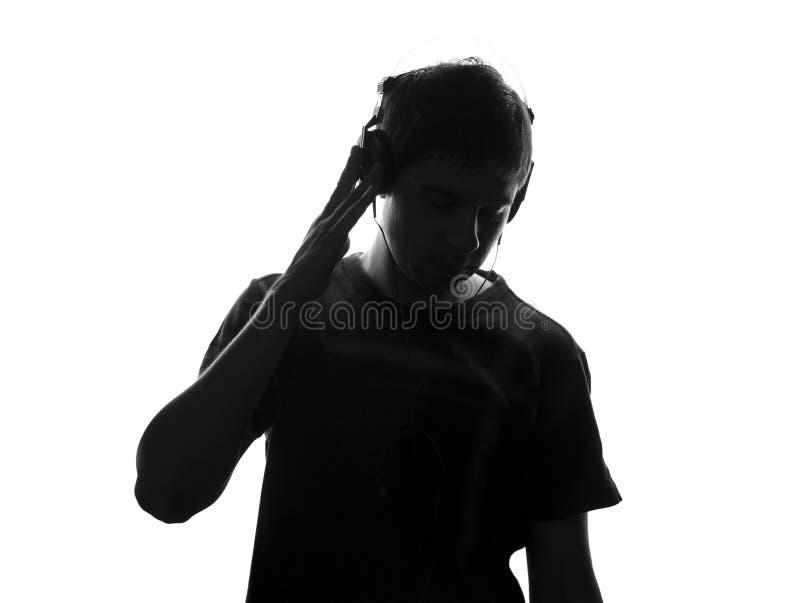 Geïsoleerd zwart-wit portret van een tiener die aan muziek in grote hoofdtelefoons luisteren stock foto's