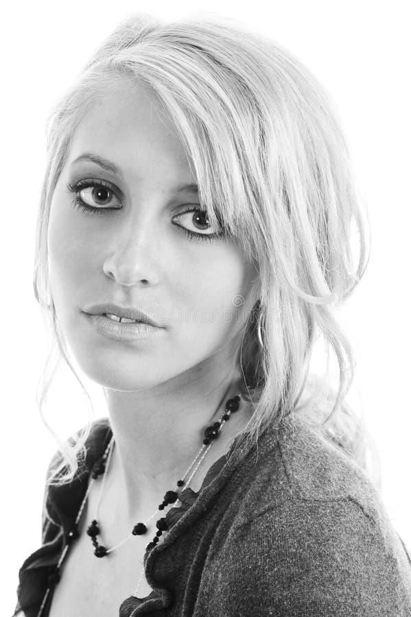 Geïsoleerde b/w-foto van een mooie jonge blondevrouw die met grote blauwe ogen camera onderzoeken royalty-vrije stock fotografie