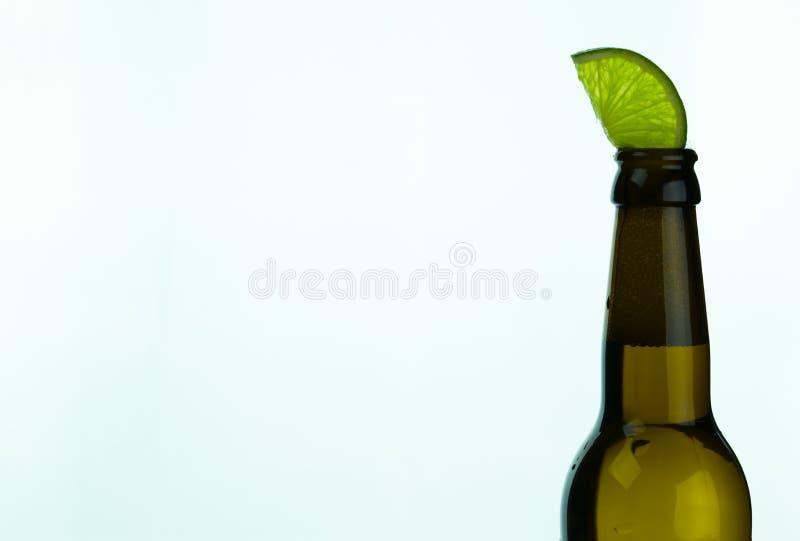 Geïsoleerde bruine bierfles met een plak van groene kalk op een witte achtergrond stock foto's