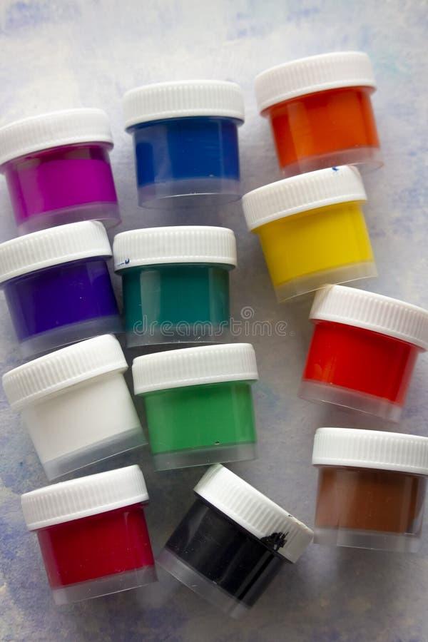 Geïsoleerde gekleurde acrylverven in de plastic flessen stock foto's