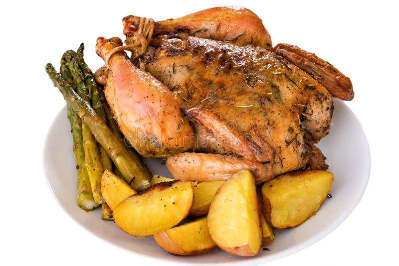 Geïsoleerde geroosterde gehele kip op een plaat stock foto