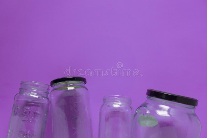 Geïsoleerde glaskruiken, vlak op violette purpere achtergrond, ruimte voor exemplaar ruimtebovenkant stock afbeeldingen