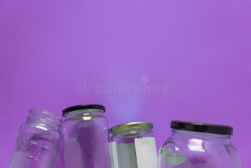 Geïsoleerde glaskruiken, vlak op violette purpere achtergrond, ruimte voor exemplaar ruimtebovenkant stock foto's