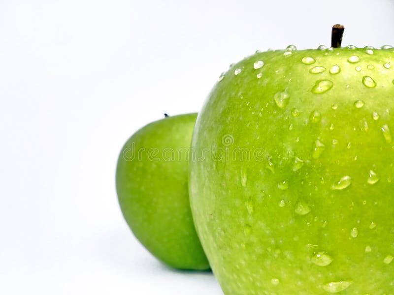 Geïsoleerde groene appel met druppeltjes stock foto's