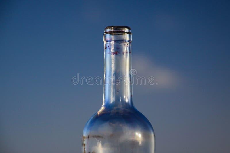 Geïsoleerde hals van lege rode wijnfles tegen blauwe avondhemel royalty-vrije stock afbeelding