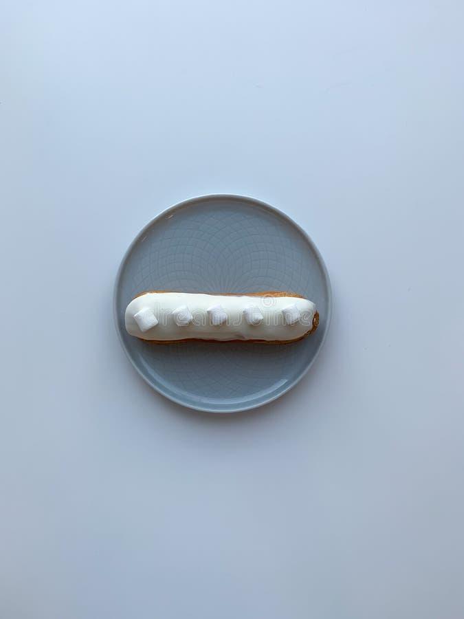 Geïsoleerde heerlijke witte room eclair met heemst op grijze lijst Dessert voor ontbijt en coffeetime Hoogste mening royalty-vrije stock foto