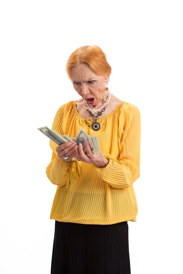 Geïsoleerde het geld van de bejaardeholding royalty-vrije stock foto's