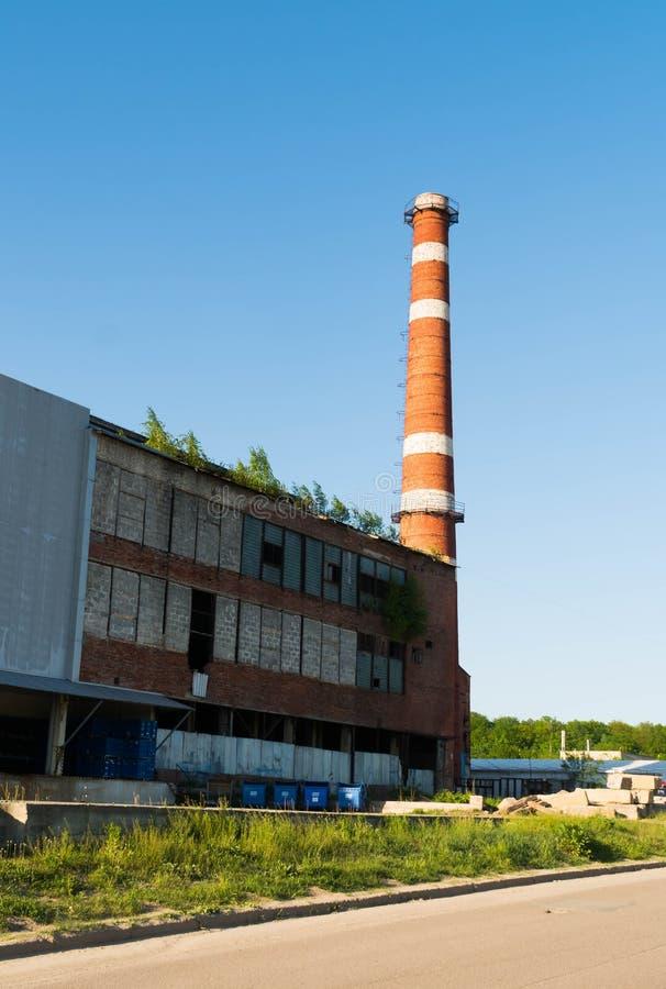 Geïsoleerde oude oude doorstane lange industriële fabrieksschoorsteen, de rode grungy wijnoogst van de baksteenschoorsteen grunge stock foto's