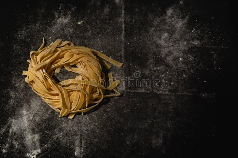 Ge?soleerde ruwe deegwaren op een zwarte achtergrond met een plaats voor tekst Traditionele Italiaanse deegwaren, noedels, taglia royalty-vrije stock afbeeldingen