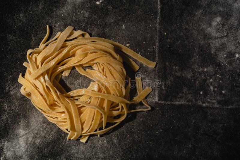 Ge?soleerde ruwe deegwaren op een zwarte achtergrond met een plaats voor tekst Traditionele Italiaanse deegwaren, noedels, taglia royalty-vrije stock foto's