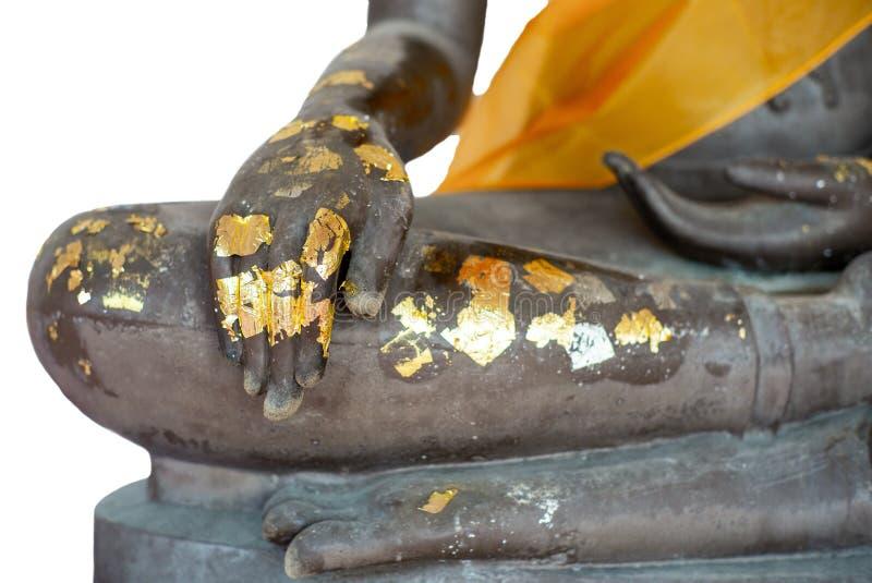 Geïsoleerde selectieve nadruk op close-uphand van het standbeeld van Boedha die door het gouden blad op witte achtergrond met een stock foto