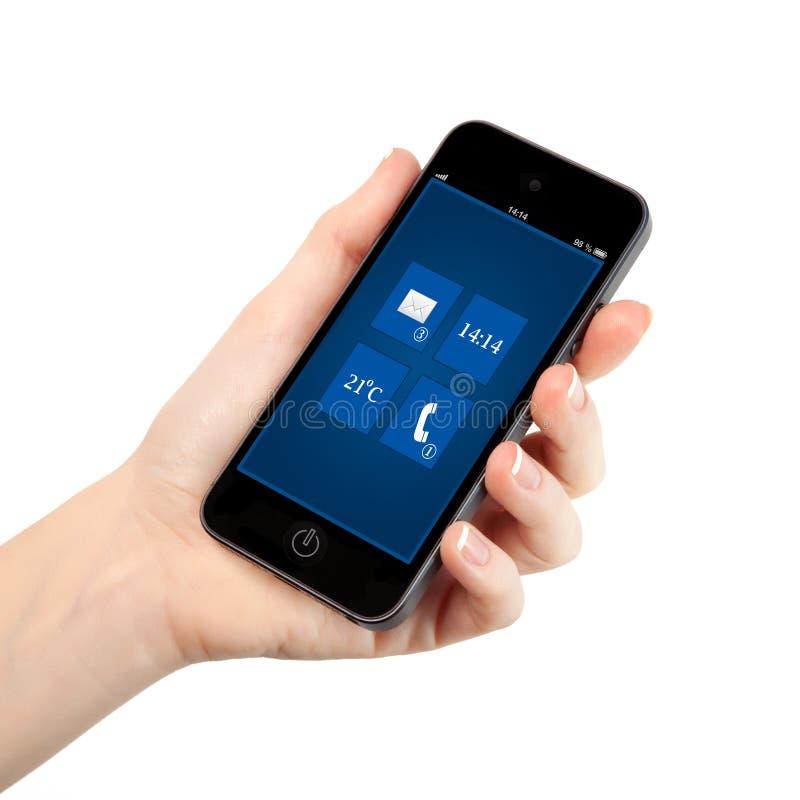 Geïsoleerde vrouwelijke hand die een telefoon met interfaceachtergrond o houden stock afbeeldingen