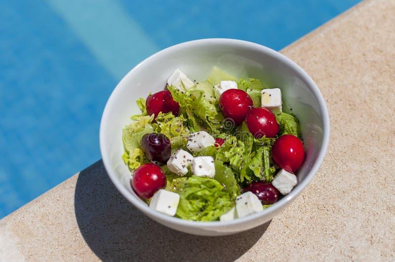 Ge?soleerde witte kom met een verse salade De sla, feta-kaas, sappige kersen, chiazaden, oilve oli?t Naast van het zwembad royalty-vrije stock afbeelding