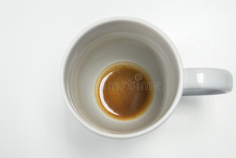 Geïsoleerde witte mok met koffievlek en residu bij bodem stock foto